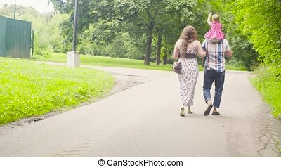 Happy parents with baby girl walking in a park - Happy...
