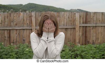 Woman crying in the garden. She is staying outdoors on a...