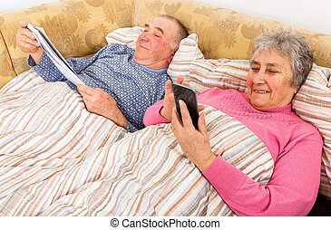 Senior man reading and his wife surfing the internet - Photo...