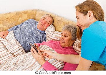 Elderly couple and young caregiver - Young caregiver helping...