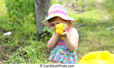 A little girl plays and laughs, shoots water from a gun