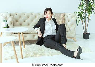 Beautiful woman sitting on the floor. - Beautiful woman in a...