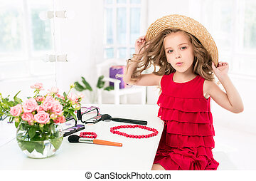 A little girl with cosmetics. She is in mother's bedroom,...