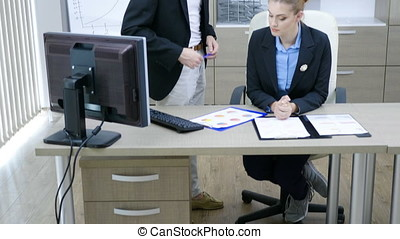Businessman and businesswoman at a desk office talking and...