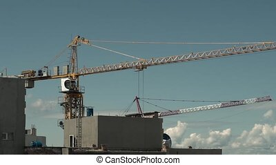 Construction Industry. Tower Crane Working Against Blue Sky...