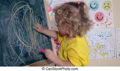creative child drawing with two chalks on blackboard. Cute...