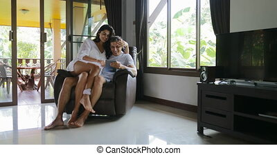 Woman And Man Sit In Armchair Kiss Using Tablet Computer...