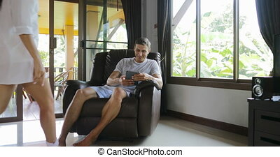 Woman Come To Man Sit In Armchair Using Tablet Computer Talking Touch Screen Browsing Online Internet, Young Couple At Home Together
