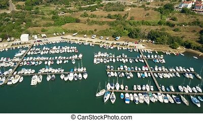 Aerial shot of parked boats and yachts at marina piers on a...