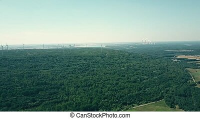 Aerial pan shot of distant smoking stacks of a traditional power plant and modern wind farm. Clean energy production concept