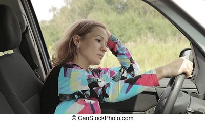 Beautiful blonde woman is driving and calling by phone