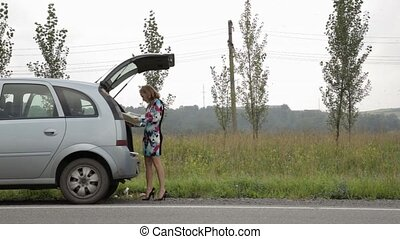 blonde girl stending near her broken car with open trunk on a country road and read the instruction