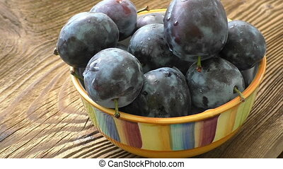Fresh organic plums in ceramic bowl on rustic wooden table