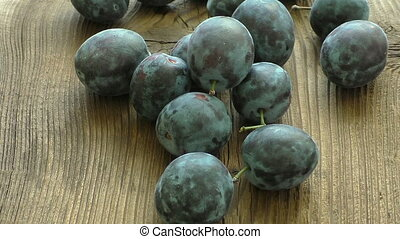 Fresh organic plums on rustic wooden table