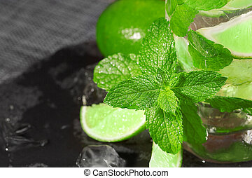 A close-up of a lime mojito. A refreshing green mojito with liquor, mint and ice. An alcoholic beverage on a wooden background.