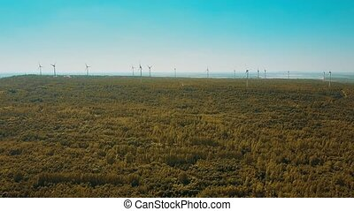 Aerial shot of wind turbines in autumn forest. Ecologic...