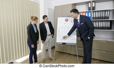 Businessman explaining on white board and drawing trends to...