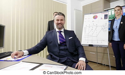 Portrait of smiling successful businessman working in his busy office with his two colleagues in the background