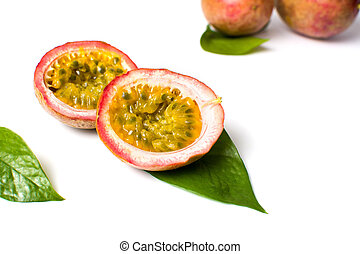 Halved passion fruit with leaves on white
