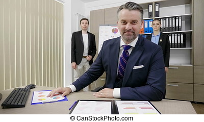 Successful businessman working in his busy office with his two colleagues in the background