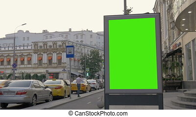A Billboard with a Green Screen on a Busy Street. People and...