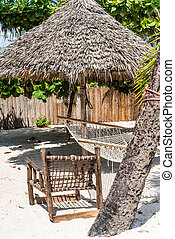 perfect place for rest on a beach with thatched umbrella, wooden chair and hammock