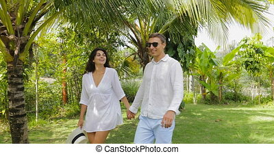 Couple Walking Holding Hands In Tropical Garden Talking,...