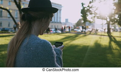 Young beautiful woman walking in the park on sunset and using the smartphone for chatting in Internet outside.