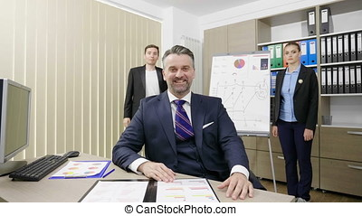Portrait of businessman working in his busy office with his two colleagues in the background