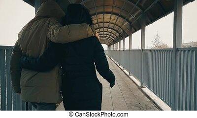Couple walking and hugging across the footbridge over...