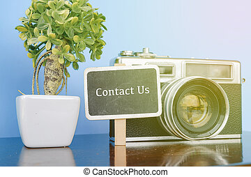 CONTACT US  word, wooden signage, vintage camera and artificial plant on wooden desk with reflection.