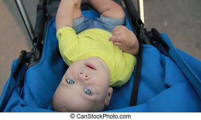 Father picking up infant son from baby stroller - Close up...