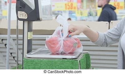 Young girl weighed on the scales of bell peppers in the supermarket stock footage video.