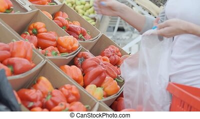 Young woman chooses paprika on store shelves. - Young woman...