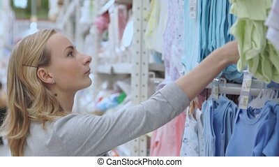 Woman Shopping in Children's Clothing Store. - Woman...