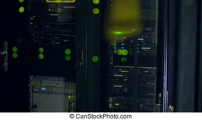 Green lights seen through network cabinets doors. - Blinking...