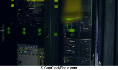 Green lights seen through network cabinets doors. - Blinking...