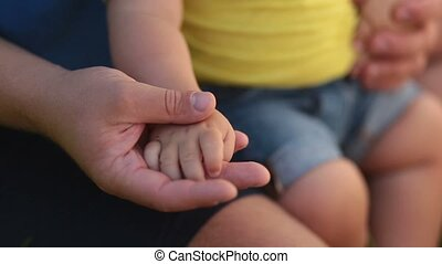 Father holding hand of infant son in his palm - Touch of...