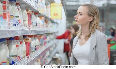 sale, shopping, consumerism people. woman with shopping basket choosing products in supermarket. Girl in market choosing bottle from the fridge