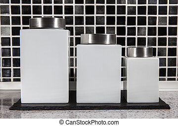 Square white storage jars in modern black and white tiled...