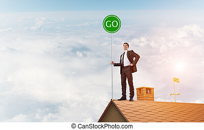 Businessman in suit on house top with ecology concept signboard. Mixed media