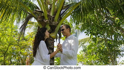 Couple Stand Under Palm Tree Kiss Talking In Tropical Garden , Happy Man And Woman Outdoors