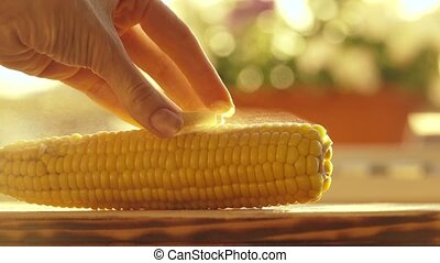 Female hand placing a piece of butter on hot freshly boiled...