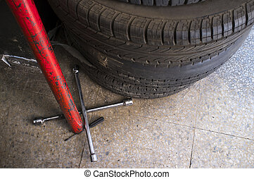 Used tyres with Fixed Cross Wheel Wrench. Changing car tire...