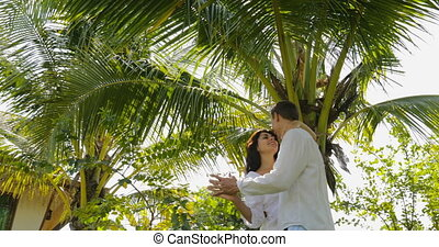 Couple Dancing Under Palm Tree In Tropical Garden Near Villa...