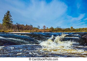 Waterfall drain on the Winnipeg River - Foam water rapids on...