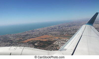 Plane is flying over the big city after takeoff. Passenger...