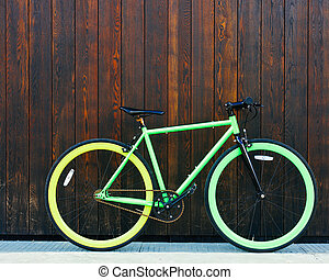 Bright green Fixed Gear beautiful vintage bicycle stands in a black wooden wall