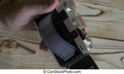 Closeup of male hands set new film. vintage camera....