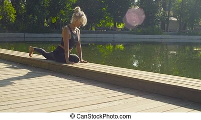 Young woman doing yoga exercises in the park - Young...